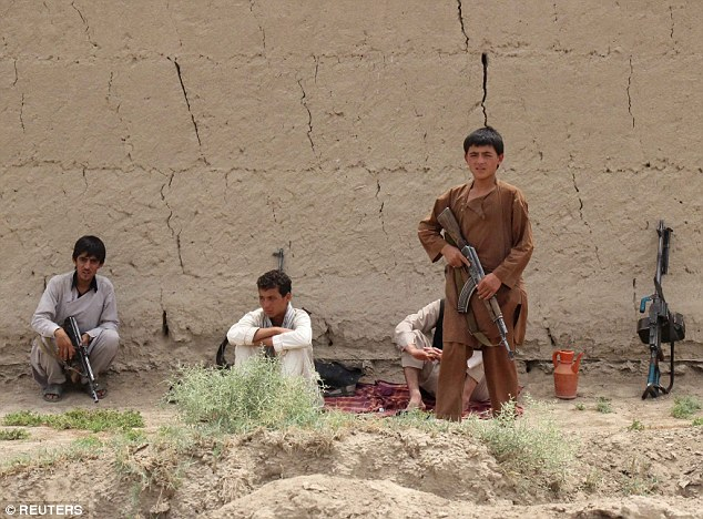 Courtesy: www.dailymail.co.uk, Young members of Afghan local police (ALP) sit near the frontline during a battle with the Taliban in Kunduz province, Afghanistan